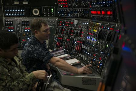 A sailor flips a switch on a large control panel for a submarine.