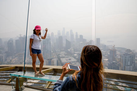 A woman poses for a photo at the top of the Space Needle. The city skyline behind her is smoky