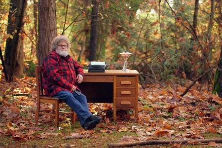 Knute Berger sits at a desk in the woods among fallen leaves