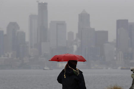 A person with an umbrella looks out to the Seattle skyline