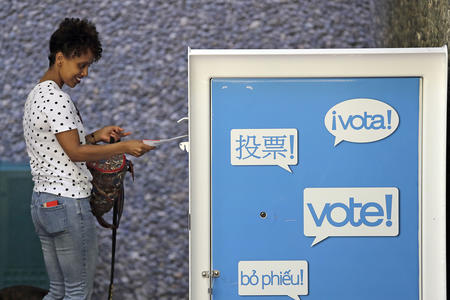 A woman puts her ballot into a ballot box