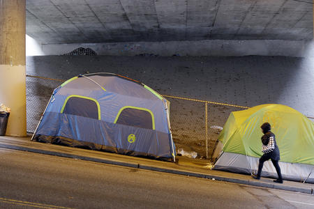 Tents line a sidewalk under a freeway overpass