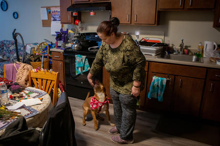 A woman plays with her dog in an apartment.