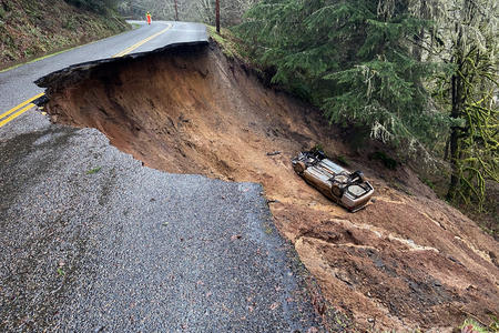a car lies in a crater created by a landslide on a rural road.