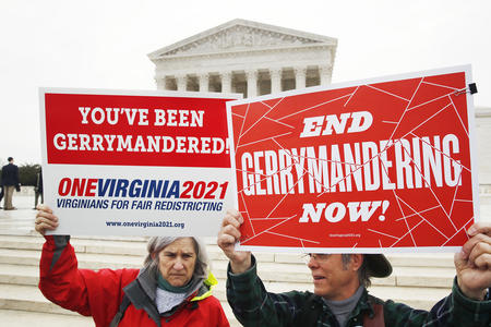 "Protesters hold signs saying ""End Gerrymandering now!"" and ""You've been gerrymandered!"""