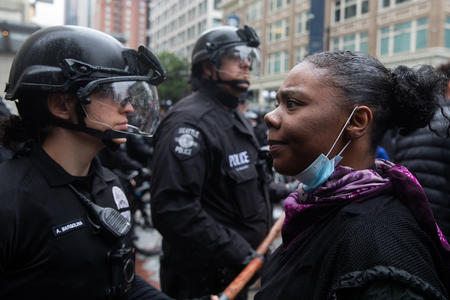 a white female police officer and a black female protester face to face