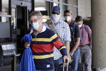Travelers wear protective masks as they wait for a shuttle after arriving at Seattle-Tacoma International Airport