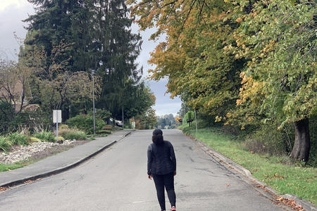 woman walking on street in fall foliage