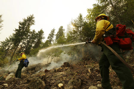 Colby Lyon, of the Central Region Strike Force Team II, sprays a hillside with water as part of the response to a fire near Chelan, Wash. on Aug. 18, 2015.