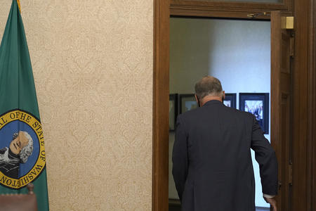 View of Jay Inslee's back as he walks through a door