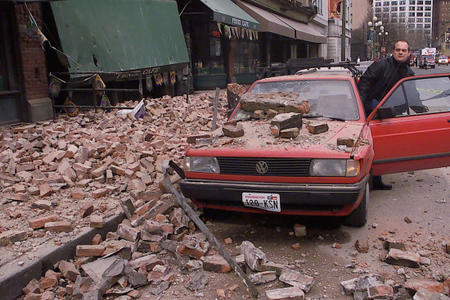 Paul Riek checks to see if his car starts after parts of the top half of a nearby building fell on it, during an earthquake in downtown Seattle, Wednesday, Feb. 28, 2001.	Credit: Stevan Morgain/AP