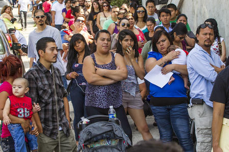FILE - In this Aug. 15, 2012, file photo, a line of people living in the U.S. without legal permission wait outside the Coalition for Humane Immigrant Rights in Los Angeles. Washington state is joining California and others in suing the Trump administration over its decision to add a question about citizenship to the 2020 U.S. Census. (AP Photo/Damian Dovarganes, File)