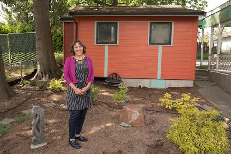 Architect Sheri Newbold stands outside her cottage in Seattle's Greenwood neighborhood, June 1, 2018.