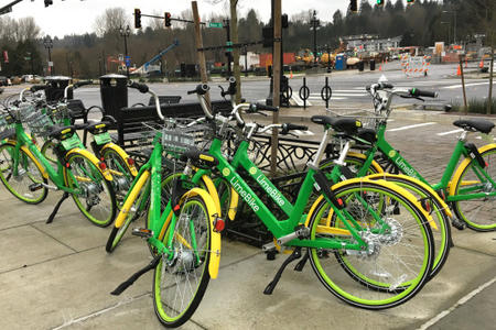 "Seven LimeBike bicycles are parked in a cluster near the corner of Bothell Way and Main Street in downtown Bothell on Thursday, Feb. 1, 2018. LimeBike said it initiated a ""gradual roll-out"" in Bothell in mid-January, the first time private bike-share has expanded into Seattle's suburbs.	Credit: Kristen M. Clark/Crosscut"