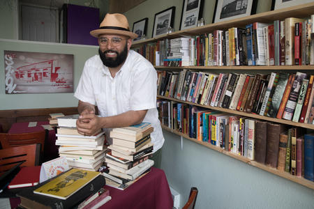 Estelita's Library owner, community organizer and activist Edwin Lindo stands along an array of books within the modest space in Seattle's Beacon Hill neighborhood, May 8, 2018.
