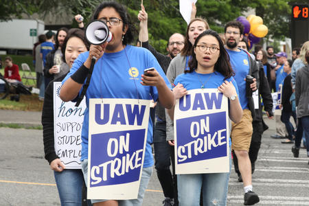 Students march across the intersection of Pend Oreille Street and Montlake Boulevard NE during one-day strike with graduate students who are represented by UAW Local 421 at the University of Washington in Seattle, May 14, 2018