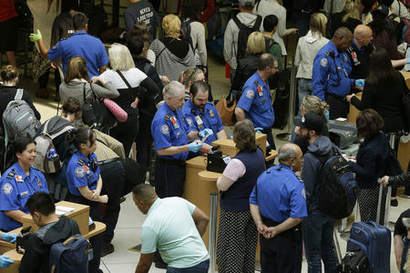 TSA agents check passenger boarding passes and identification at a security screening checkpoint, Thursday, May 19, 2016, at Seattle-Tacoma International Airport in Seattle. Airport officials announced Thursday that following a training period, several dozen contract employees will start work on Monday, May 23, 2016 to assist passengers at security checkpoints, with the goal of freeing up TSA agents and reducing passenger wait times. (AP Photo/Ted S. Warren)