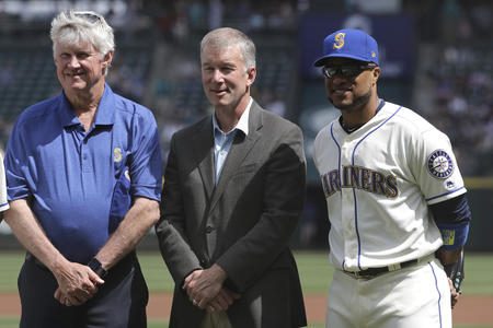 Seattle Mariners owner and chairman John Stanton, left, and President Kevin Mather, center, stand with Robinson Cano during a ceremony before a baseball game against the Los Angeles Angels, Sunday, May 6, 2018, in Seattle. (AP Photo/Ted S. Warren)