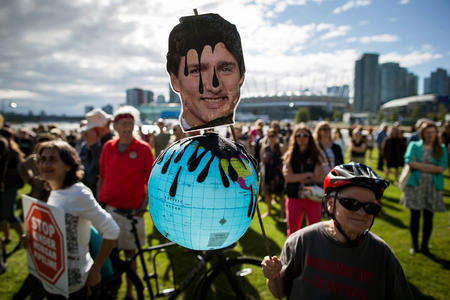 A protester holds a photo of Canadian Prime Minister Justin Trudeau and a representation of the globe during a protest against the Kinder Morgan's Trans Mountain pipeline expansion, in Vancouver, British Columbia, Tuesday, May 29, 2018. Canada's federal government said Tuesday it is buying the controversial pipeline from the Alberta oil sands to the Pacific Coast to ensure it gets built. (Darryl Dyck/The Canadian Press via AP)