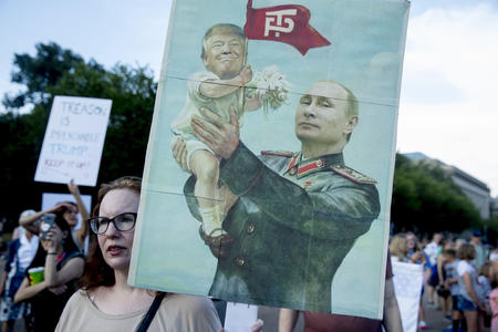 A woman holds a sign depicting Russian President Vladimir Putin and President Donald Trump during a protest outside the White House, Tuesday, July 17, 2018, in Washington. (AP Photo/Andrew Harnik)