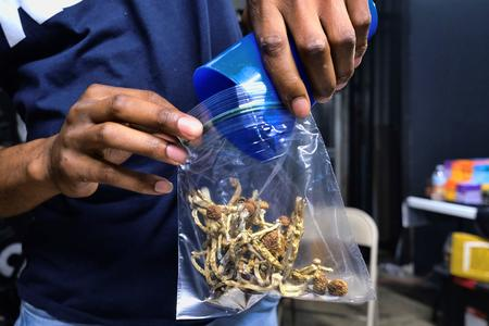 A man scoops mushrooms out of a clear baggie.