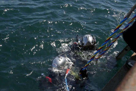 Two divers wearing metal helmets descend into the ocean