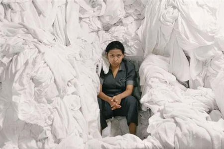 A woman sits in a pile of laundry
