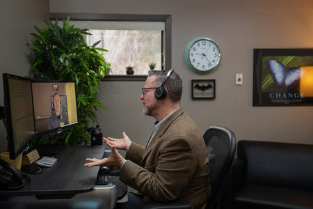 Wayne Pollard video chats with Dr. Matthew Iles-Shih on his computer