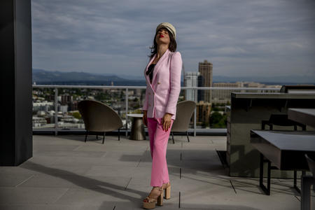 Venus Aoki stands on a rooftop, looking upward, in pink jacket and trousers with cap