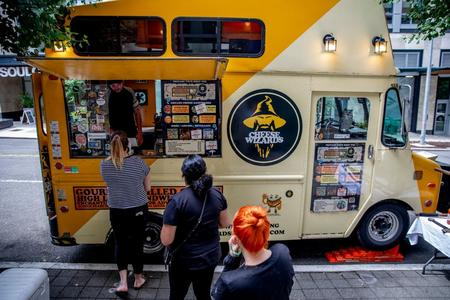 People line up on a sidewalk in front of a yellow food truck called Cheese Wizards, which sells grilled cheese sandwiches.
