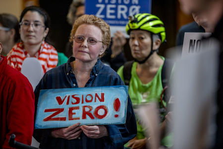 Woman protestor in crowd holding sign reading vision zero
