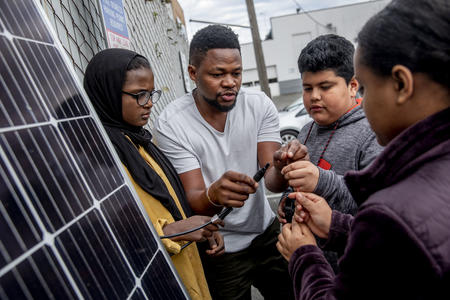 Edwin Ngugi Wanji, center, teaches a group of kids from the Lake City Young Leaders program about how to work a solar panel at the Lake City Community Center on April 1.
