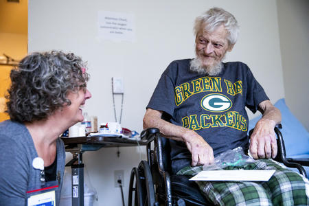 Chuck King laughs with his hospice nurse Laura Newcomb