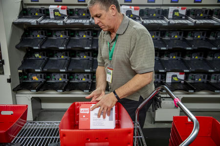 An election worker handles ballots in a red sorting tray.