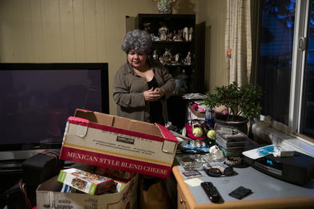 Irma Serrano packs thing into a box in her living room