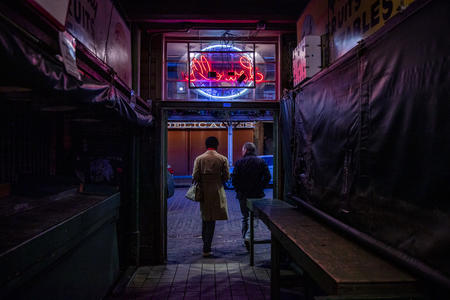 two people walk through doorway under neon sign
