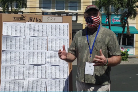 Doug Ericksen stands in front of a poster talking about the voting process in El Salvador, with palm trees and buildings behind him