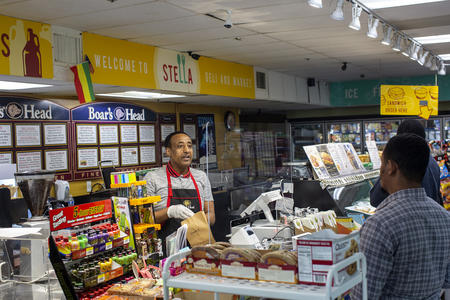 Shoppers at Stella's Deli wait at the counter