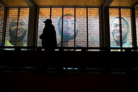 Man walks by portraits of formerly incarcerated black men