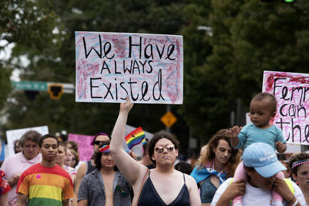 "A person in a crowd holds a sign that reads ""We have always existed."""