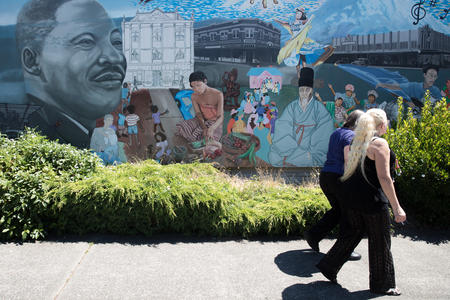 Women walk by a mural in Tacoma's Hilltop neighborhood.