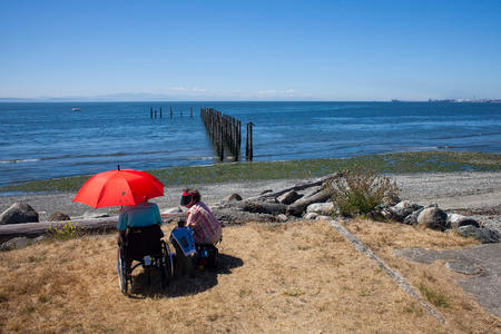 Two people sit on a beach in Point Roberts, Washington