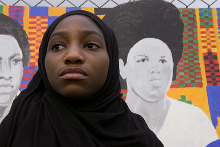 A Franklin High School student stands in front of a mural.