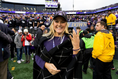 "University of Washington Athletic Director Jennifer Cohen flashes a ""W"" sign at Husky Stadium"