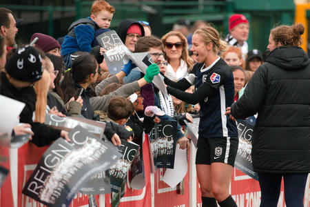 A Reign FC soccer player signs autographs for fans on the sideline.