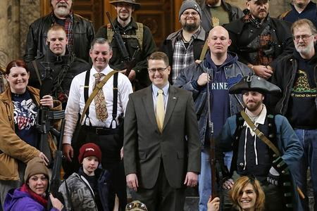 Matt Shea smiles in the House gallery, surrounded by people open carrying firearms
