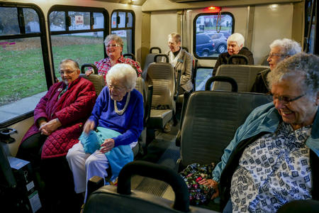 Seven older women enjoy a laugh while riding in a transit van