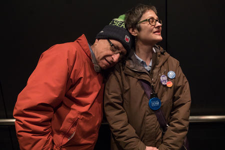 Rafe Schwimmer rests his head on the shoulder of his wife Paula while in an elevator at Seattle City Hall.