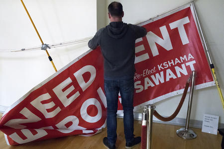 A man takes down a sign encouraging rent control