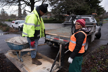 Seattle Conservation Corps crew member Chris Townsell (left) is lowered on a truck lift with a wheel barrow by crew member April Winfrey (right) at Angel Morgan P-Patch Community Gardens in Seattle's Rainier Valley